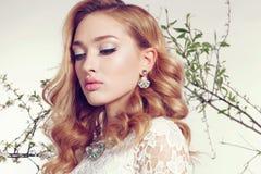 Junge Frau mit dem blonden gelockten Haar trägt elegantes Spitzekleid und -Juwel Stockbild