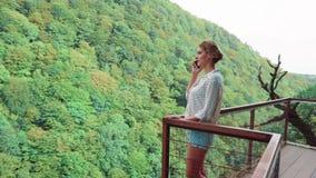 Junge Frau mit dem blonden Haar in der hellen weißen Tupfenbluse auf Brücke über Okat-Schlucht und spricht telefonisch, Schießen stock video