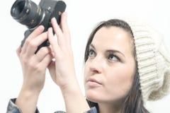 Junge Frau mit dem braunen Haar hält Kamera Lizenzfreies Stockfoto