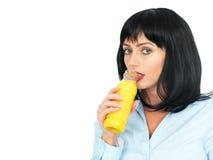 Junge Frau mit dem dunklen Haar Orangensaft von einer Flasche trinkend Stockfotografie