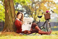 Junge Frau mit dem Fahrrad, das auf einem Gras sitzt und ein newspa liest Stockfotografie