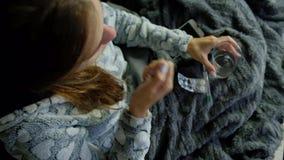 Junge Frau mit dem Fieber, das Pillen nimmt stock video