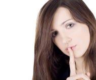 Junge Frau mit dem Finger auf Lippen über Weiß Stockfotografie