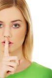 Junge Frau mit dem Finger auf Lippen Lizenzfreie Stockbilder