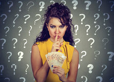 Junge Frau mit dem Finger auf Lippen gestikulieren und Eurobanknoten in der Hand Lizenzfreie Stockfotos