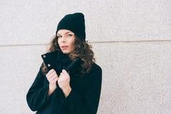 Junge Frau mit dem gelockten Haar in einem schwarzen Mantel lizenzfreie stockbilder