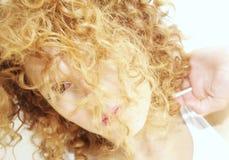 Junge Frau mit dem Gesicht versteckt durch lockiges Haar Stockfoto