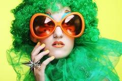 Junge Frau mit dem grünen Haar und den carnaval Gläsern Stockfoto