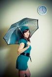 Junge Frau mit dem grünen Kleid, das unter Wanduhr aufwirft Lizenzfreie Stockfotografie