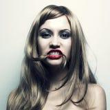 Junge Frau mit dem Haar in einem Mund Stockbild