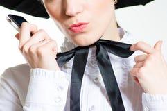 Junge Frau mit dem Handy, der schwarzes u. weißes Kleid des viktorianischen Stils trägt Stockfoto