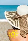 Junge Frau mit dem Hut, der auf dem Strand sitzt stockbild