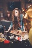 Junge Frau mit dem Kater, der am unordentlichen Tisch nach Partei sich lehnt Lizenzfreie Stockbilder