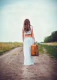 Junge Frau mit dem Koffer in der Hand, der durch Feldweg weggeht Stockbild