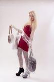 Junge Frau mit dem langen blonden Haar und drei Handtaschen in der Hand Lizenzfreies Stockfoto