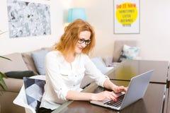 Junge Frau mit dem langen roten Haar und den Gläsern für Ansichtarbeiten, Drucke auf einer grauen Laptoptastatur, die an einem Ho lizenzfreie stockfotografie