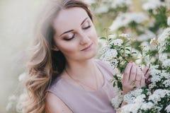 Junge Frau mit dem langen schönen Haar in einem Chiffon- Kleid, das mit lilacin Garten mit weißen Blumen aufwirft Stockbilder