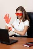 Junge Frau mit dem Laptop in den Handschuhen und in der Orange Stockbilder