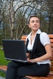 Junge Frau mit dem Laptop, der auf Bank sitzt Stockfoto