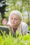 Junge Frau mit dem Laptop, der auf dem Gras liegt Stockbild