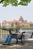 Junge Frau mit dem Laptop, der auf der Bank sitzt. Stockfoto