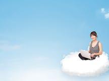 Junge Frau mit dem Laptop, der auf Wolke mit Kopienraum sitzt Lizenzfreies Stockfoto