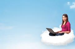 Junge Frau mit dem Laptop, der auf Wolke mit Kopienraum sitzt Lizenzfreie Stockfotografie