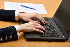Junge Frau mit dem Laptop - Innen Frauen übergibt das Arbeiten mit Laptop, Dokument und Stift auf einem Hintergrund Lizenzfreies Stockbild