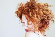 Junge Frau mit dem lockigen roten Haar, das schüchtern ist Stockfotografie