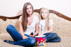Junge Frau mit dem Mädchen, das den Spaß sitzt hat u. den Film, Popcorn, glückliche lächelnde u. schauende Kamera essend aufpasst Lizenzfreies Stockbild
