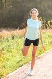 Junge Frau mit dem perfekten dünnen Körper, der ihr Bein ausdehnt stockfotografie