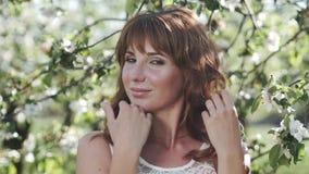Junge Frau mit dem roten Haar, das an der Kamera im blühenden Garten aufwirft stock video