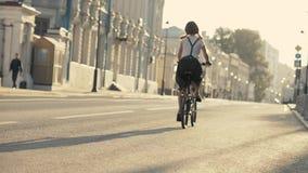 Junge Frau mit dem roten Haar, das ein Fahrrad in der Ansicht von unten des Parks reitet Frauenfahrradpark lizenzfreies stockfoto