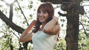 Junge Frau mit dem roten Haar, das sich herum, werfend im geblühten Garten dreht auf stock video footage