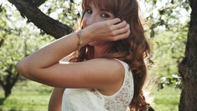 Junge Frau mit dem roten Haar, das sich herum, werfend im geblühten Garten dreht auf stock video