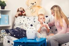 Junge Frau mit dem Sohn, der zu Hause Einatmung mit einem Zerstäuber tut stockbilder