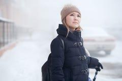 Junge Frau mit dem Spaziergänger, der durchdacht in Winter, Blicke am Himmel geht stockbilder