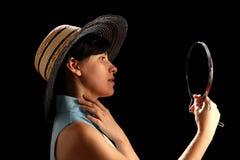 Junge Frau mit dem Strohhut, der auf Spiegel schaut Stockfotografie