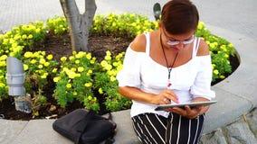 Junge Frau mit dem Tablet-Computer, der im Stadtpark sitzt stock footage
