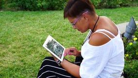 Junge Frau mit dem Tablet-Computer, der im Stadtpark sitzt stock video