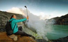 Junge Frau mit dem Wanderer, der selfie auf Spitzenvulkan nimmt lizenzfreie stockfotografie