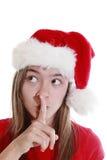 Junge Frau mit dem Weihnachtshut, der Ruhe signalisiert Lizenzfreie Stockfotos