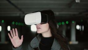Junge Frau mit dem wellenartig bewegenden Haar unter Verwendung der Gläser einer virtuellen Realität auf Parkplatz Mädchen, das d stock footage