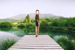 Junge Frau mit den angehobenen Armen oben auf dem Naturhintergrund Lizenzfreies Stockfoto