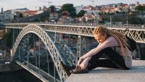 Junge Frau mit den blonden Dreadlocks, die auf dem Hintergrund von Brücke Dom Luiss I, Porto sitzen Lizenzfreie Stockfotografie