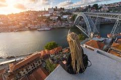 Junge Frau mit den blonden Dreadlocks, die auf Standpunkt vor Duero-Fluss und Brücke Dom Luis I in Porto sitzen Stockfoto