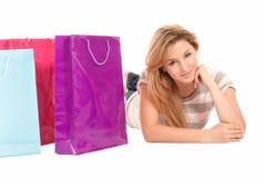 Junge Frau mit den Einkaufenbeuteln, die auf Fußboden liegen Lizenzfreies Stockfoto