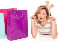 Junge Frau mit den Einkaufenbeuteln, die auf Fußboden liegen Stockfotos