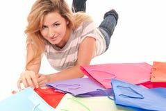 Junge Frau mit den Einkaufenbeuteln, die auf Fußboden liegen Lizenzfreie Stockfotografie