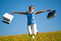 Junge Frau mit den Einkaufstaschen, die in eine Wiese springen Stockbild
